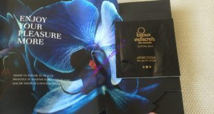 Black product leaflet opening to reveal a blue orchid, with sample attached for Bijoux Indiscrets Aphrodisia Orgasm Enhancer Balm