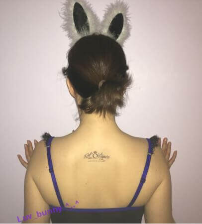 Back of Luv Bunny's Head with bunny ears, wearing a Hot Octopuss tattoo between her shoulder blades
