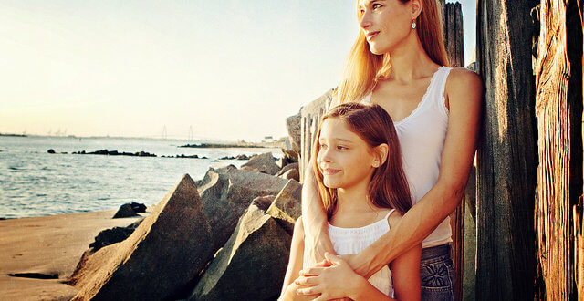 Parenting: Mother & Daughter standing and looking along a beach.