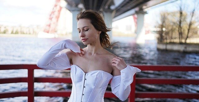 Romantic corset-clad girl under a bridge