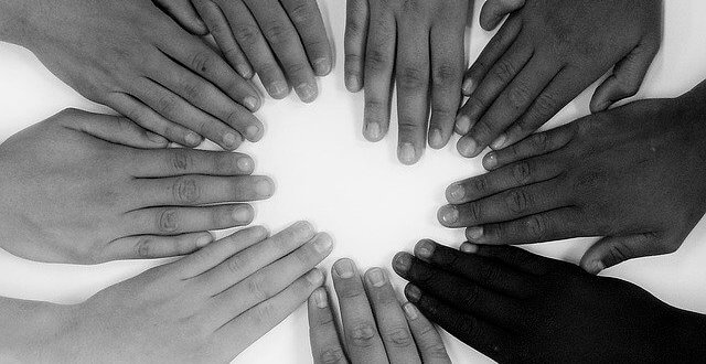 hands from various ethnicities arranged in a circle and using a filter to show it doesn't matter if you're black or white