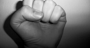 Black and white photo of a clenched fist to show anger