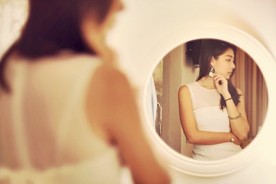 young woman's reflection in a round mirrormirror