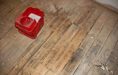 dust on a wooden floor with a mop bucket