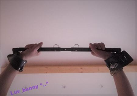 Luv Bunny's wrists shackled with a spreader bar, held up in the air.
